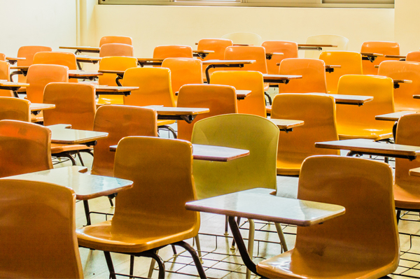 A brightly lit classroom with empty student desks.