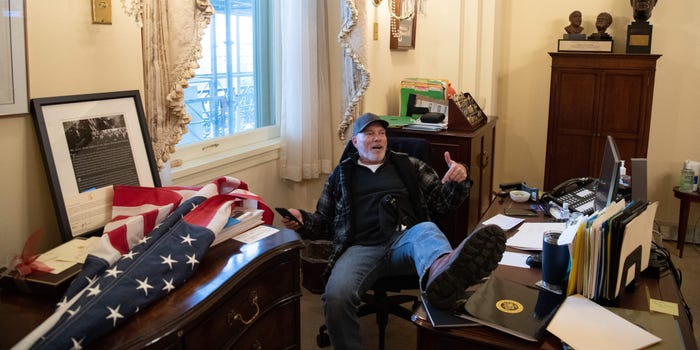 Trump supporter sits at Nancy Pelosi's desk after breaking into the Capitol