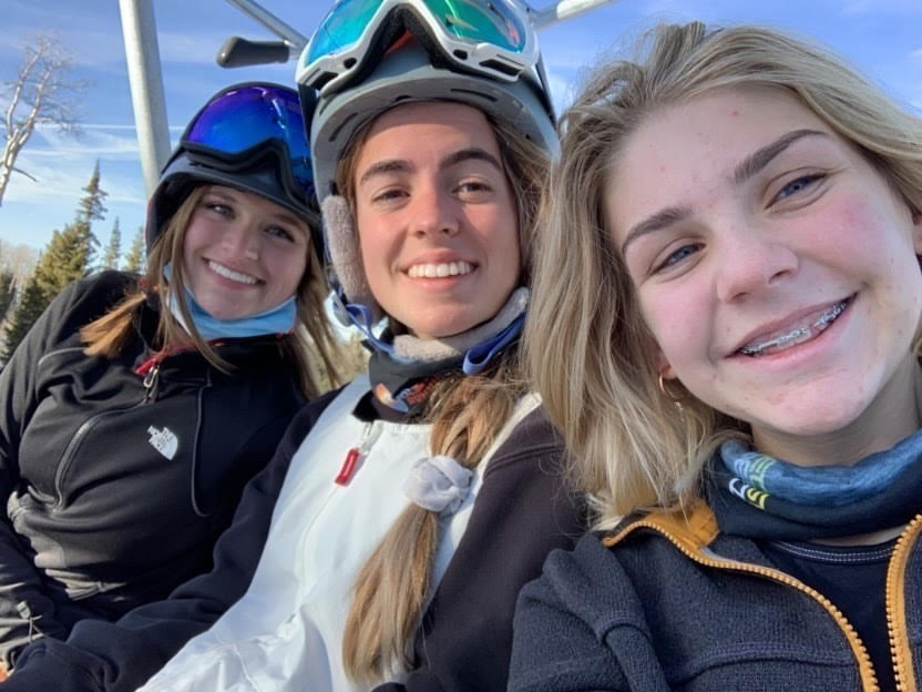 Ellie Reese, Isabella Stosich, and Ali Walnum posing for a picture on the ski lift