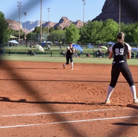 Hailey Morrow, junior, throwing the ball to one of her teammates at a softball game