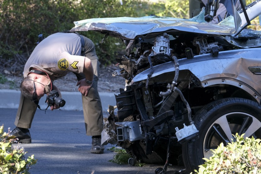 A police officer inspects the damage to the automobile.