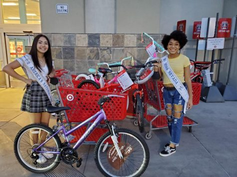 Aiyanna Castro (left) and Bella Hawkins (right) show their shopping cart full of donations.